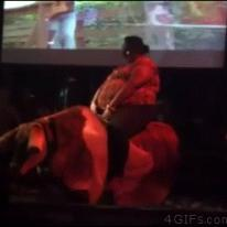 A rotund woman rolls off of a mechanical bull.