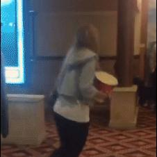 A clumsy girl spills all her popcorn while falling.