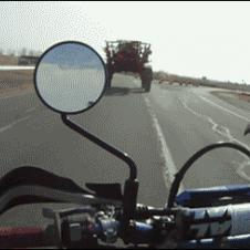 Motorcycle passes underneath tractor.