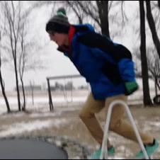 A guy jumps onto a trampoline covered in ice